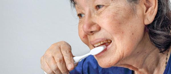 Elderly woman brushing her teeth