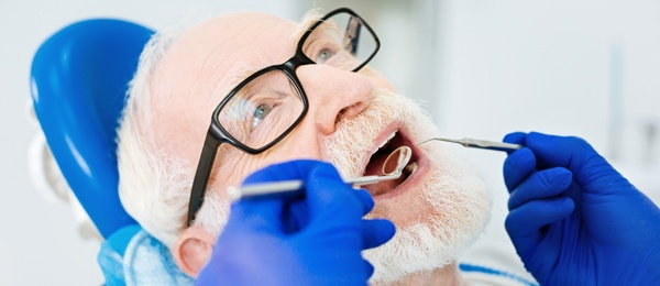 Elderly man getting his mouth examined