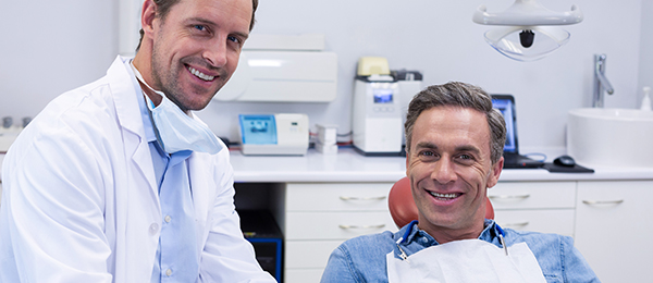 Smiling dentist with senior smiling patient